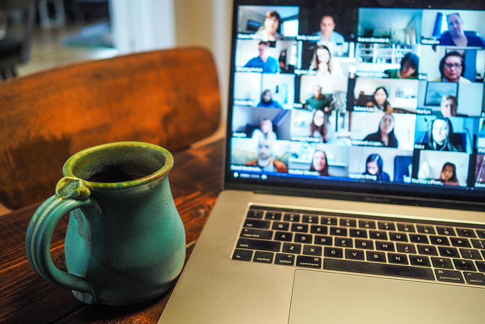 Photo of a table set up with a coffee mug on the left and a laptop on the right that shows a video conference on screen