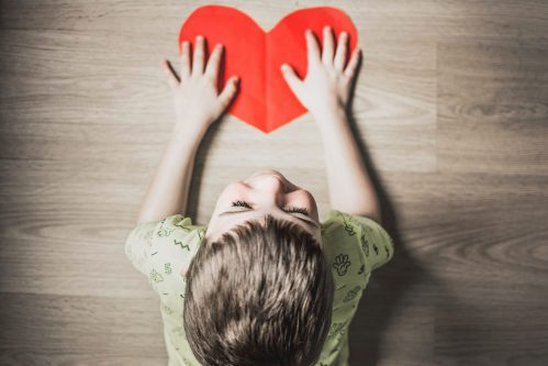 Little blond child on his hand on a red paper heart